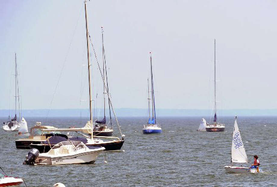 A small sailboat makes its way through other boats moored in Greenwich Harbor, off the coast of Greenwich. Photo: File Photo / Greenwich Time File Photo