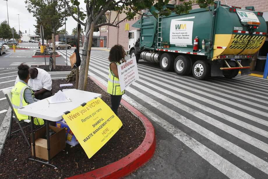 California Waste Solutions workers at Walmart on Edgewater Drive in Oakland ask passersby to withdraw their support for Waste Management's referendum to overturn the city contract. Photo: Terray Sylvester, The Chronicle