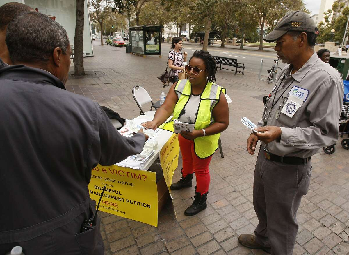 Working in support of California Waste Services in downtown Oakland on Thursday, Alayhe McCall asked Dana Suttice (left) and Ruben Rodriguez (right) not to support Waste Management's referendum.