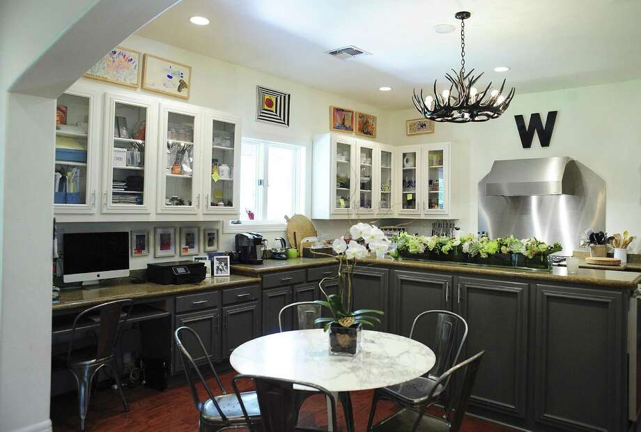 Rich oak floors add warmth, with white cabinets with glass panels and creamy white walls creating an overall feel of lightness. Photo: Billy Calzada / San Antonio Express-News / San Antonio Express-News