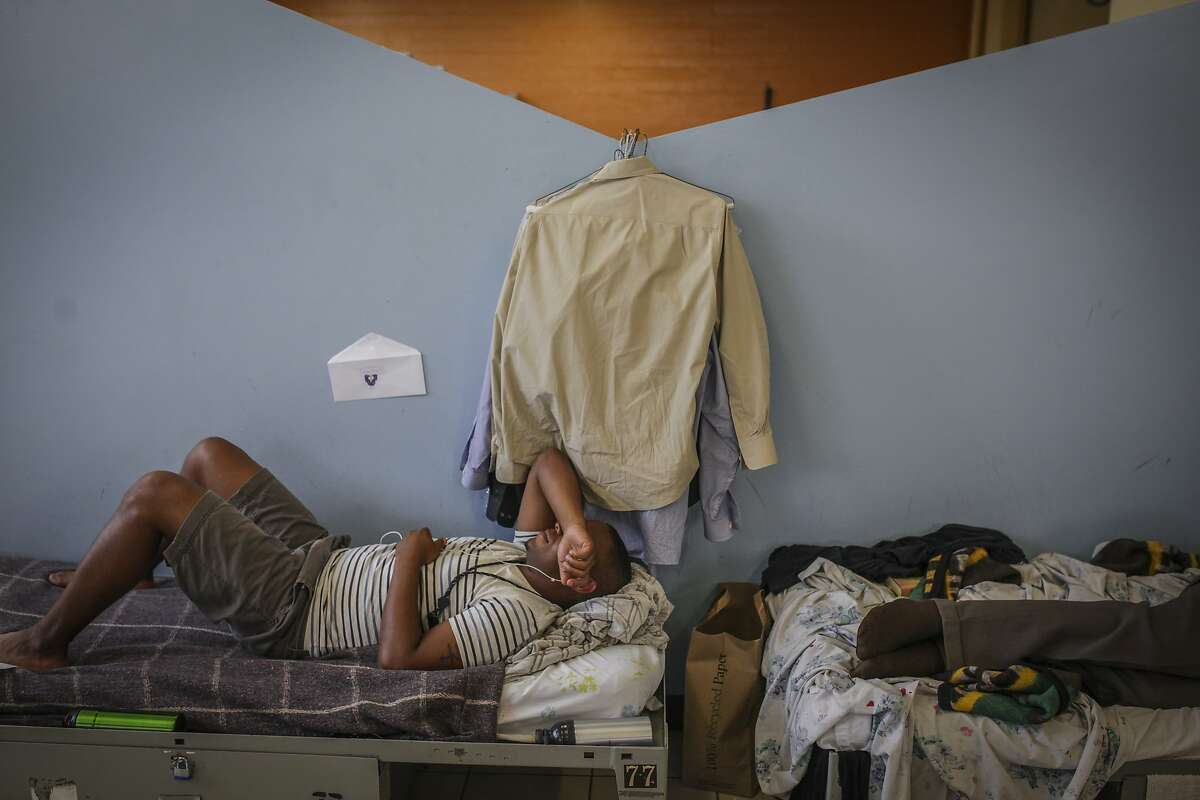 Denver Williamson, a resident at Next Door Shelter, a homeless shelter located in the city center, listens to music on his bed, on September 17th 2014. The shelter averages two to three ambulance visits a day. The city center receives the most 911 calls for the entire city.