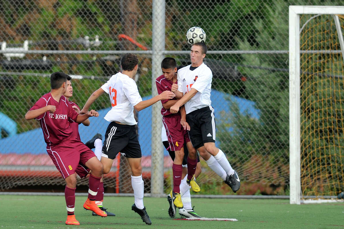 St. Joseph's Luca Imbimbo and Stamford's Michael Nunziante leap for the head ball resulting in an own-goal from Nunziante during their soccer game at Stamford High School in Stamford, Conn., on Thursday, Sept. 18, 2014. St. Joseph won, 3-0.