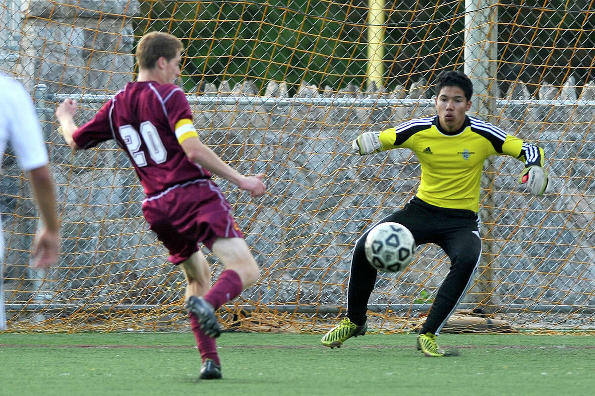 St. Joseph's Brian McBride shoots and scores on Stamford goalie Nai Perez during their soccer game at Stamford High School in Stamford, Conn., on Thursday, Sept. 18, 2014. St. Joseph won, 3-0.