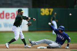 OAKLAND, CA - SEPTEMBER 18:  Eric Sogard #28 of the Oakland Athletics throws over Ryan Rua #16 of the Texas Rangers but not in time to complete the double play at first base in the top of the fourth inning at O.co Coliseum on September 18, 2014 in Oakland, California.  (Photo by Thearon W. Henderson/Getty Images)