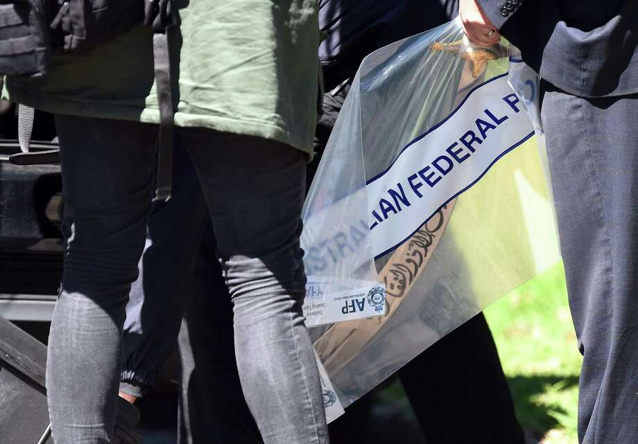 Police remove a sword as part of evidence found at a residential property in the suburb of Marsfield, in Sydney, Australia, Thursday, Sept. 18, 2014. Police said they thwarted a plot to carry out beheadings in Australia by supporters of the radical Islamic State group, by detaining 15 people and raiding more than a dozen properties across Sydney. (AP Photo/AAP Image, Paul Miller) AUSTRALIA OUT, NEW ZEALAND OUT, PAPUA NEW GUINEA OUT, SOUTH PACIFIC OUT, NO SALES, NO ARCHIVES Photo: Paul Miller, STR / AAP