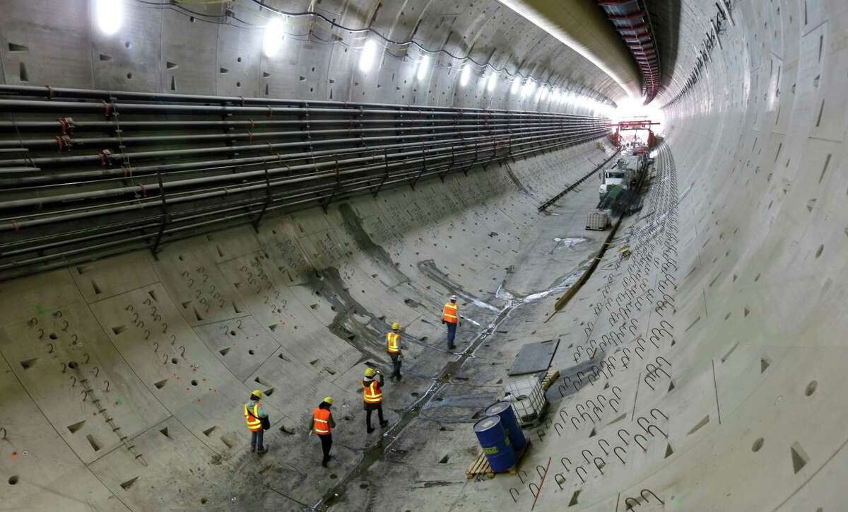 Visitors walk through the tunnel being constructed to replace the Alaskan Way Viaduct, during a media tour in Seattle on Thursday, Sept. 18, 2014. Progress on the 2-mile tunnel that will move State Route 99 underground stalled in December 2013 after the tunnel boring machine had to be shut down for repairs, but work on tunnel walls and other structures continued.