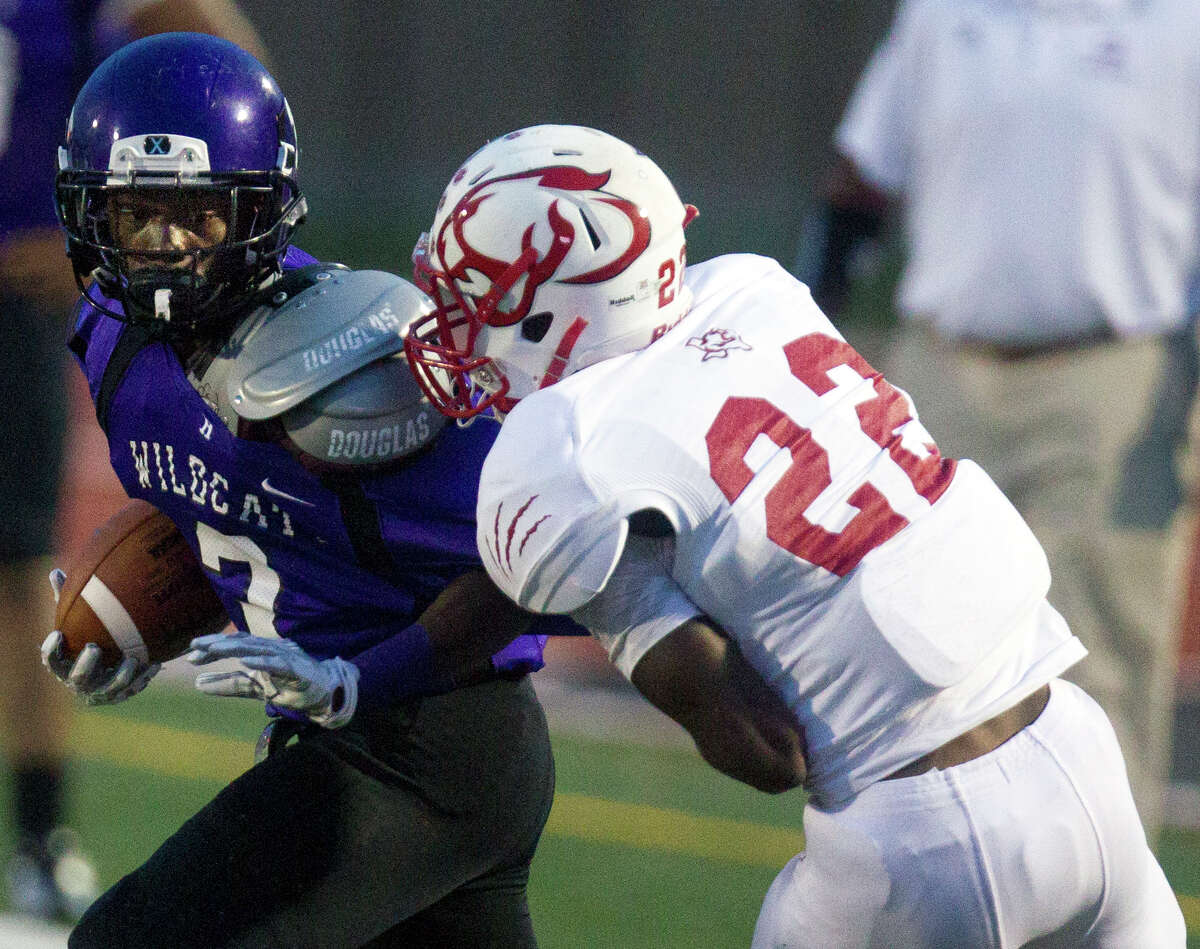 Humble High School's Carl Jordan, is brought down by Crosby High School's Joseph Pickney, right, during the first half of a football game at Turner Field, Thursday, Sept. 18, 2014, in Humble.
