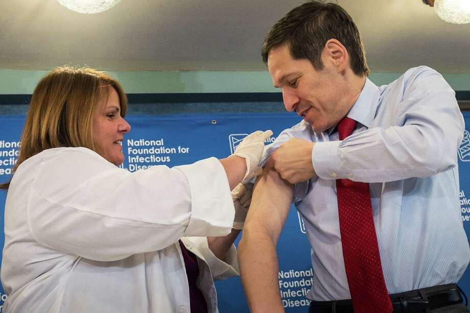 "Dr. Thomas Frieden, director of the Centers for Disease Control and Prevention, receives a flu shot from Sharon Bonadies at the conclusion of a news conference at the National Press Club in Washington, Thursday, Sept. 18, 2014.  ""Vaccination is the single most important step everyone 6 months of age and older can take to protect themselves and their families against influenza,"" said Frieden.  Influenza hospitalized a surprisingly high number of young and middle-aged adults last winter, and this time around the government wants more of them vaccinated. (AP Photo/J. David Ake) ORG XMIT: DCDA104 Photo: J. David Ake / AP"
