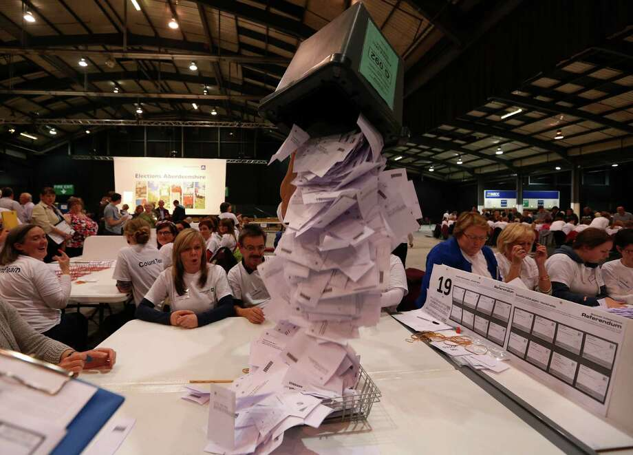 Ballot boxes are opened as counting begins in the Scottish Independence Referendum for the Aberdeenshire Council area, Aberdeen, Scotland, Thursday, Sept. 18, 2014. As the polls closed late Thursday and the vote counting began, many Scots settled in to stay up all night in homes and bars to watch the results. A nationwide count began immediately at 32 regional centers across Scotland. (AP Photo/Scott Heppell) ORG XMIT: NSH181 Photo: Scott Heppell / AP