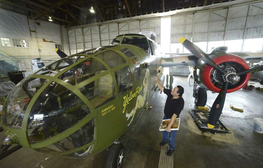 Fernando Cortez works on the nose art of Yellow Rose, a B-25 Mitchell bomber used as a trainer during WWII. Photo: Photos By Billy Calzada / San Antonio Express-News / San Antonio Express-News