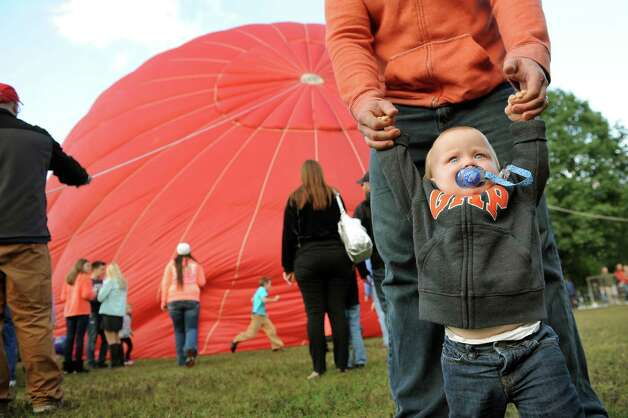 The Re/Max balloon rises behind Max Smith, 1, of Fort Edward and his father, Lucas Smith, during the 42nd annual Adirondack Balloon Festival on Thursday, Sept. 18, 2014, at Crandall Park in Glens Falls, N.Y. (Cindy Schultz / Times Union) Photo: Cindy Schultz / 00028662A