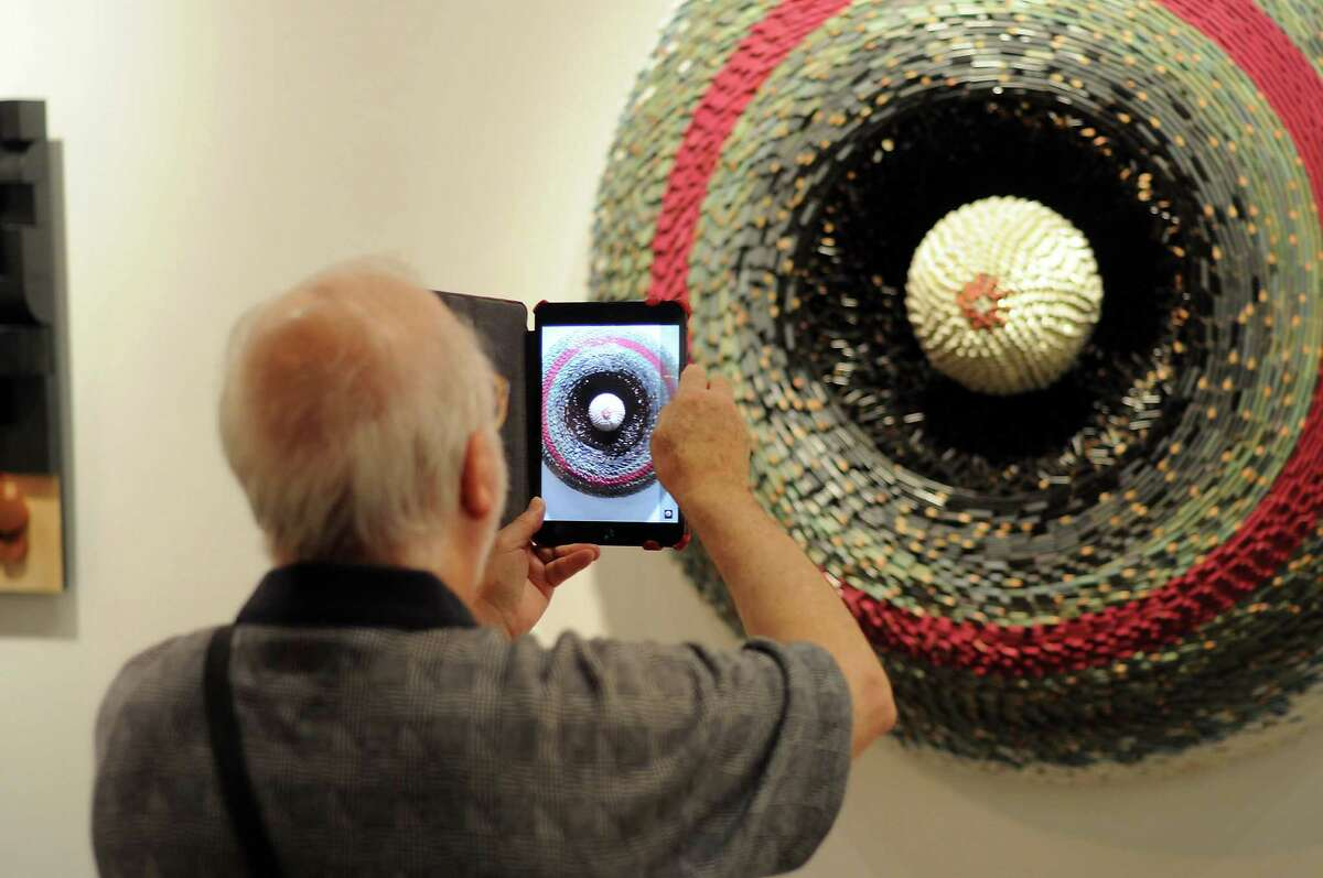 A guest shoots a photo of artwork at the preview party for the Houston Fine Art Fair.