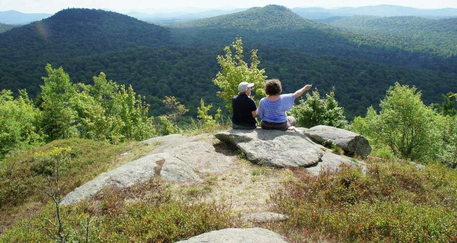A hiker points toward the Bog River from the summit of Goodman Mountain. (Herb Terns/Times Union) Photo: Picasa