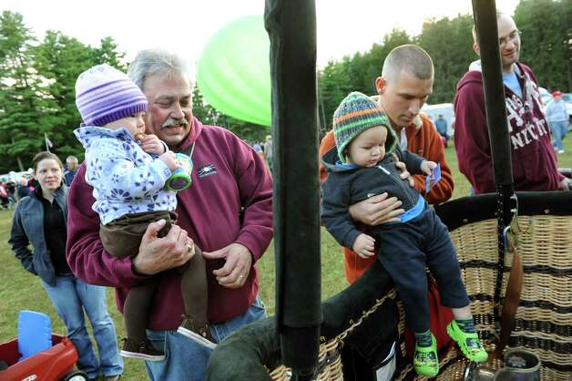 Warren Kelly of Hudson Falls, left, holds his friend Evelyn Anderson, 19 months, as they look over the Patriot's Dream balloon basket with Nathan Sumner-Beckwith, 18 months, of Glens Falls and his uncle Nick Sumner during the 42nd annual Adirondack Balloon Festival on Thursday, Sept. 18, 2014, at Crandall Park in Glens Falls, N.Y. (Cindy Schultz / Times Union) Photo: Cindy Schultz / 00028662A