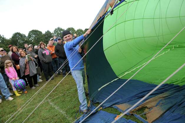 Merrill Carpenter of Glens Falls, center, helps hold the Limelight balloon as it fills with air during the 42nd annual Adirondack Balloon Festival on Thursday, Sept. 18, 2014, at Crandall Park in Glens Falls, N.Y. (Cindy Schultz / Times Union) Photo: Cindy Schultz / 00028662A
