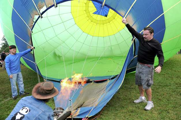 Merrill Carpenter of Glens Falls, left, and Keith Bender of Queensbury, right, hold the Limelight balloon as pilot Keith Sproul of North Brunswick, N.J. blasts propane during the 42nd annual Adirondack Balloon Festival on Thursday, Sept. 18, 2014, at Crandall Park in Glens Falls, N.Y. (Cindy Schultz / Times Union) Photo: Cindy Schultz / 00028662A
