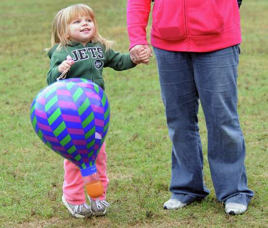 Gabrielle Graham, 3, of Glens Falls bounces with her inflatable toy hot-air balloon during the 42nd annual Adirondack Balloon Festival on Thursday, Sept. 18, 2014, at Crandall Park in Glens Falls, N.Y. Joining her is her mother, Darla Graham. (Cindy Schultz / Times Union) Photo: Cindy Schultz / 00028662A