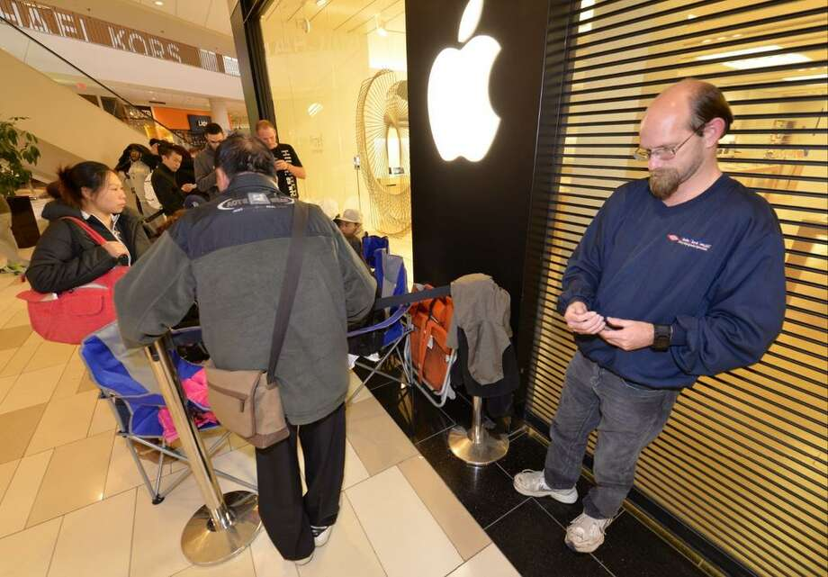 Brian Wheeler waits for his new IPhone 6 on Friday. He stood in line since 6 a.m. Thursday. (Skip Dickstein /Times Union)