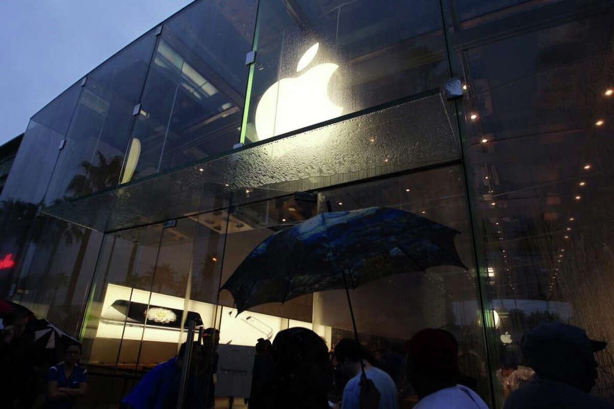 People stand in line to buy the iPhone 6 in the rain at Highland Village in Houston, Sept. 19, 2014.