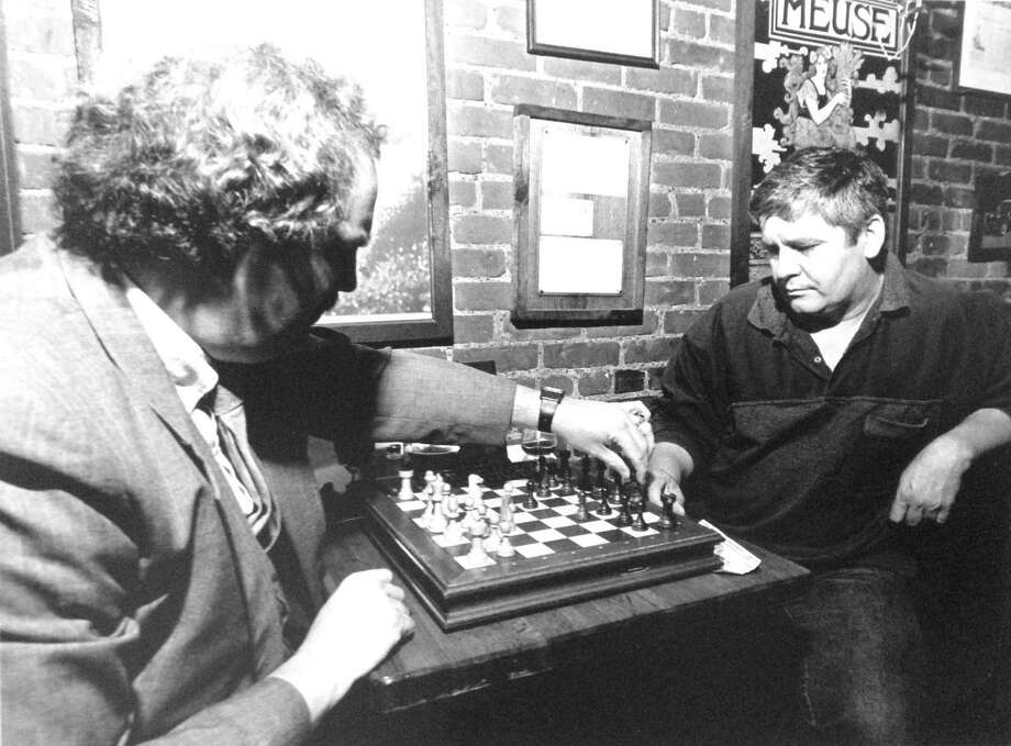 Chess players Bill Dykstra and Ivan Capin ponder their strategies during a game night at the former Apple's Cafe on Atlantic Street in downtown Stamford on Sept. 25, 1989. Photo: File Photo / Stamford Advocate File Photo