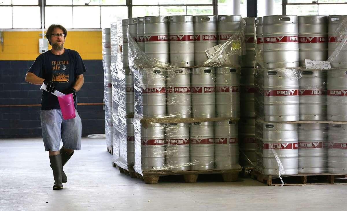 Jason Davis, Head Brewer at Freetail Beer, carries sanitizing liquid as he walks past empty kegs.