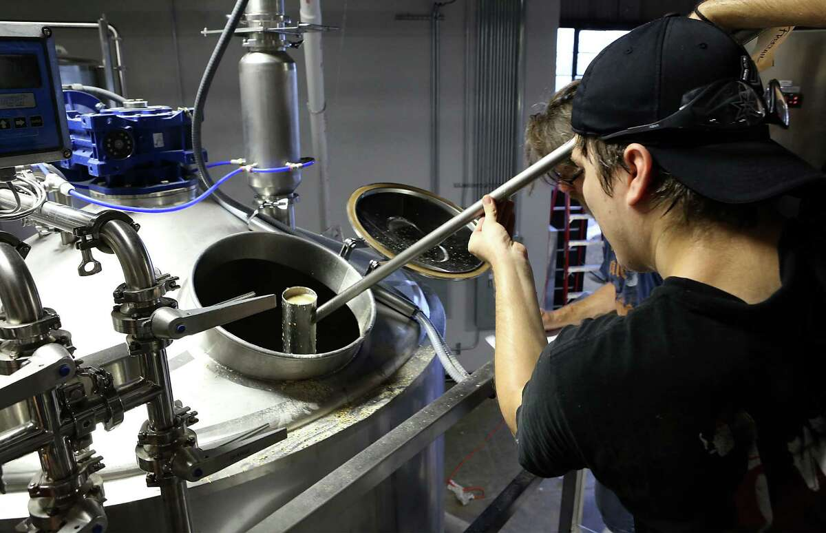 Nicholas Adcock, Assistant Brewer at Freetail Beer, uses a dipping cup to check the temperature in the mash tank.
