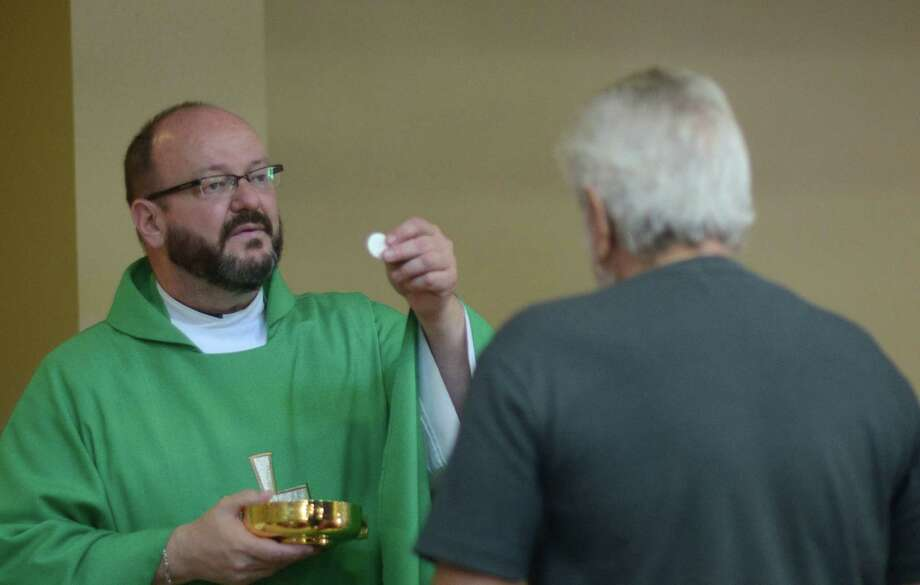 Father Kevin Fausz, the new pastor of Our Lady of Perpetual Help Catholic Church on Grimes Street in the East Side, gives Holy Communion on Tuesday, Aug. 5, 2014. Photo: Billy Calzada, San Antonio Express-News / San Antonio Express-News