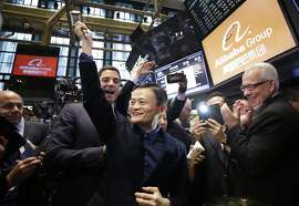 "Jack Ma, center, founder of Alibaba, raises a ceremonial mallet before striking a bell during the company's IPO at the New York Stock Exchange, Friday, Sept. 19, 2014 in New York. The stock is to start trading Friday under the ticker ""BABA."" (AP Photo/Mark Lennihan)"