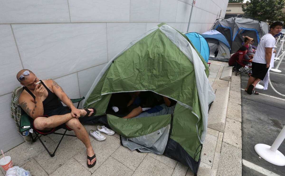 Tri Nguyen looks at his iPhone while camped out for the iPhone 6 at the Apple Store at Highland Village on Westheimer Road in Houston, Tx. The iPhone 6 will be released Friday morning.