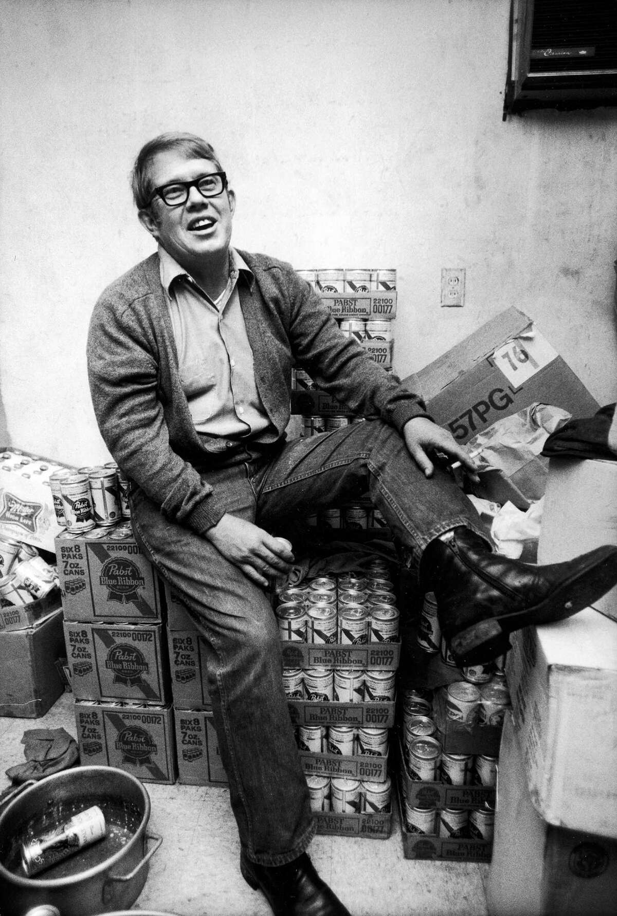 American entrepreneur Billy Carter (1924 - 1988) smokes and sits on a pile of boxes of Pabst Blue Ribbon beer in the back room of his gas station after his defeat in a mayoral election, Plains, Georgia, December 6, 1976. The younger brother of American President Jimmy Carter, Carter went on to produce his own beer brand.