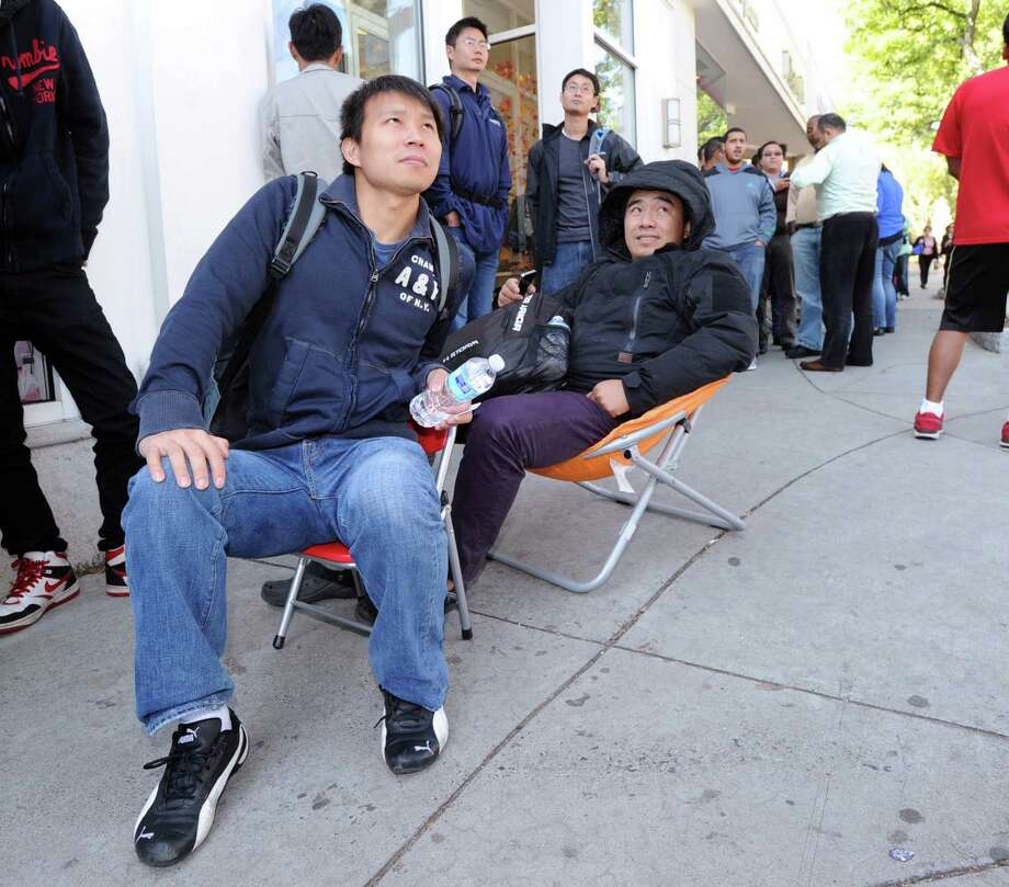 Friends, Jason Chen, left, of Queens, N.Y., and Tommy Huang of the Bronx, N.Y., sit on portable chairs while waiting to buy their iPhone 6 Plus smartphones, outside the Apple store at 356 Greenwich Ave., Greenwich, Conn., Friday, Sept. 19, 2014. The iPhone 6 and iPhone 6 Plus went on sale prompting the usual long lines for first day sales of new Apple smartphones. Photo: Bob Luckey / Greenwich Time
