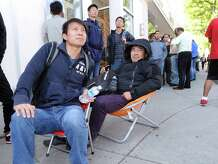 Friends, Jason Chen, left, of Queens, N.Y., and Tommy Huang of the Bronx, N.Y., sit on portable chairs while waiting to buy their iPhone 6 Plus smartphones, outside the Apple store at 356 Greenwich Ave., Greenwich, Conn., Friday, Sept. 19, 2014. The iPhone 6 and iPhone 6 Plus went on sale prompting the usual long lines for first day sales of new Apple smartphones.