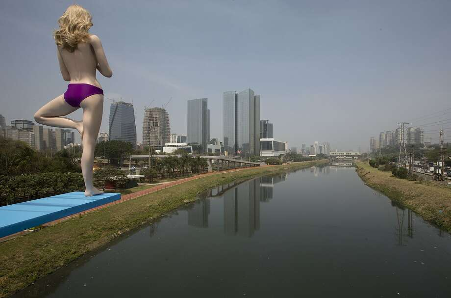 Dive in! It's not refreshing at all: A topless mannequin prepares to take the plunge into the highly polluted Pinheiros River in 