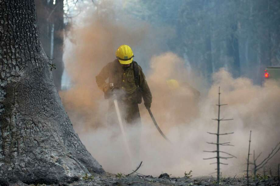 A US Forest Service crew from Plumas County cleans up along Wentworth Springs Road near Uncle Tom's Cabin in El Dorado County on Thursday, Sept. 18, 2014. The King fire has burned over 70,000 acres. The wind-whipped fire burned through 114 square miles and was 10 percent contained, according to California Department of Forestry and Fire Protection. Photo: Randall Benton, AP / The Sacramento Bee