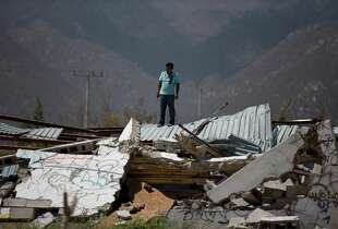 A man stands on top of a collapsed warehouse, looking for building material to salvage after Hurricane Odile destroyed his home, in San Jose de los Cabos, Mexico, Thursday, Sept. 18, 2014. Water and electricity service remained out and phone service was intermittent. Electric commission officials said some 2,500 power poles were toppled by Odile, which struck late Sunday as a Category 3 storm.