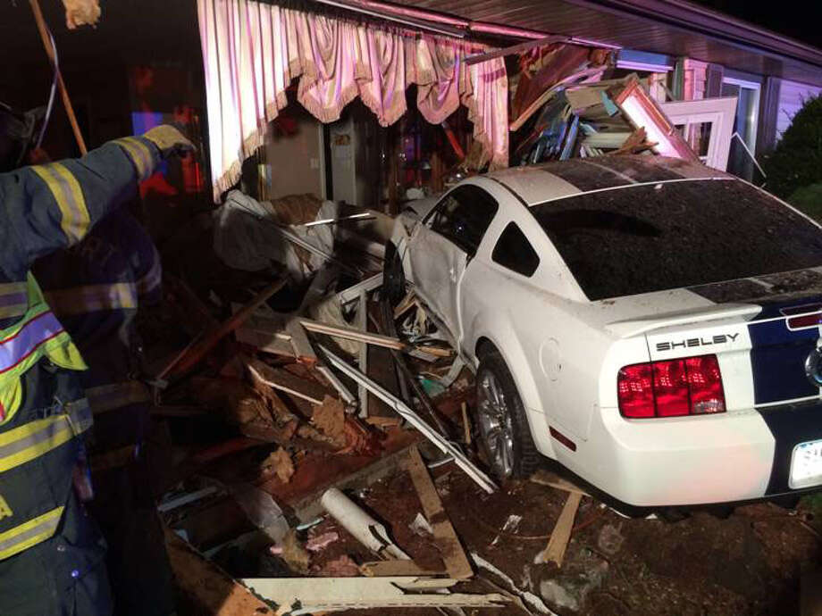 A white Shelby Mustang crashed into the  living room of a house at 3558 Old Town Rd in Bridgeport, Conn. on Thursday, Sept. 18, 2014. The house is owned by Oscar Raposo. Photo: Contributed Photo / Connecticut Post Contributed