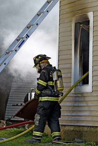 Firefighters from the City of Rensselaer and mutual aid companies work to put out a 2 alarm fire at 1808 4th Street Friday afternoon Sept 19, 2014, which left 5 adults and one child homeless in Rensselaer, N.Y.    (Skip Dickstein/Times Union) Photo: SKIP DICKSTEIN