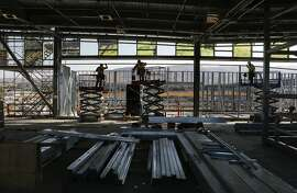 Construction workers at the Warm Springs BART station, as seen on Friday Sept. 19, 2014, in Fremont , Calif. Art glass by artist Catherine Widgery is seen above.