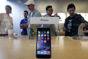 Customers try out the new iPhone 6 and 6+ after the gadgets went on sale at the Apple Store on Chestnut Street in San Francisco, Calif. on Friday, Sept. 19, 2014.
