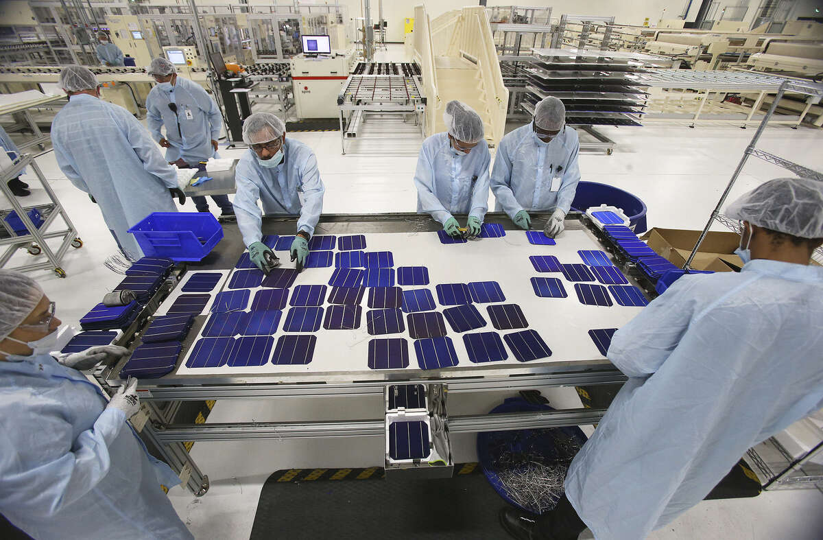 Mission Solar Energy employees gather to reconstruct damaged panels. The plant is located at Brooks City Base.
