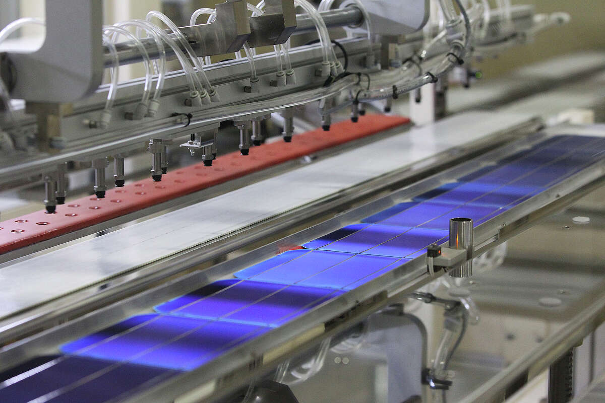 Wafers pass through on a conveyor as Mission Solar produces solar panels at its Brooks City Base location in San Antonio on September 16, 2014.