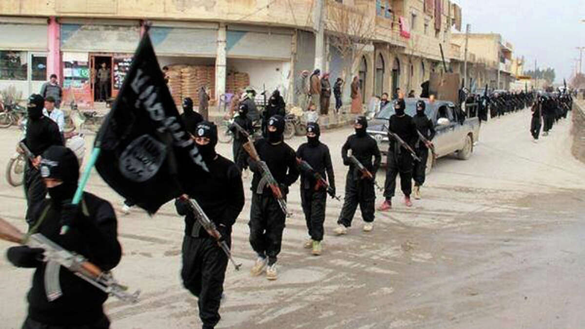 The Islamic State terror group, whose members marched through Raqqa, Syria, in this undated photo, makes as much as $3 million a day selling oil on the black market.