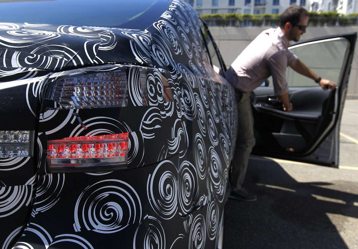 Toyota senior engineer Jared Farnsworth climbs out of a camouflaged