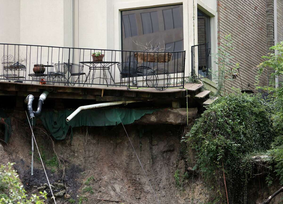 One of the Memorial Woods Town Homes looses its backyard after a part of the property collapses into the Spring Branch Bayou due to heavy rains and erosion on Friday, Sept. 19, 2014, in Houston.