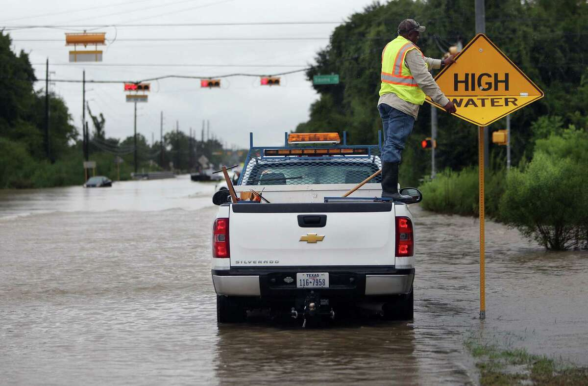 A city worker switches the sign to warning motorist of high water in the area, near the intersection of Greenhouse Road and Saums Road, where several cars stalled earlier in the day on Friday, Sept. 19, 2014, in Katy. Heavy rains cause South Mayde Creek to overflow from its banks and flood the surrounding area.