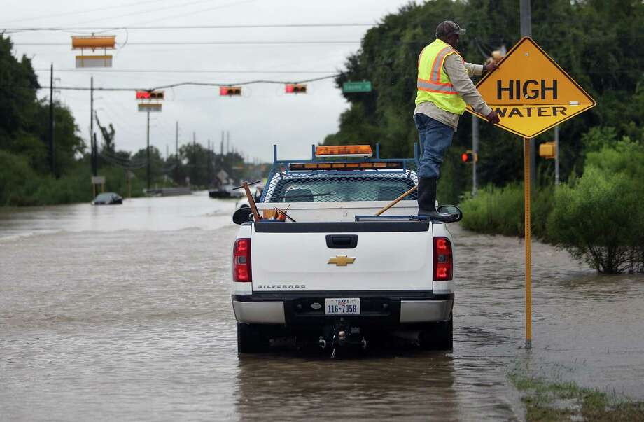A city worker switches the sign to warning motorist of high water in the area, near the intersection of Greenhouse Road and Saums Road, where several cars stalled earlier in the day on Friday, Sept. 19, 2014, in Katy. Heavy rains cause South Mayde Creek to overflow from its banks and flood the surrounding area. Photo: Mayra Beltran, Houston Chronicle / © 2014 Houston Chronicle