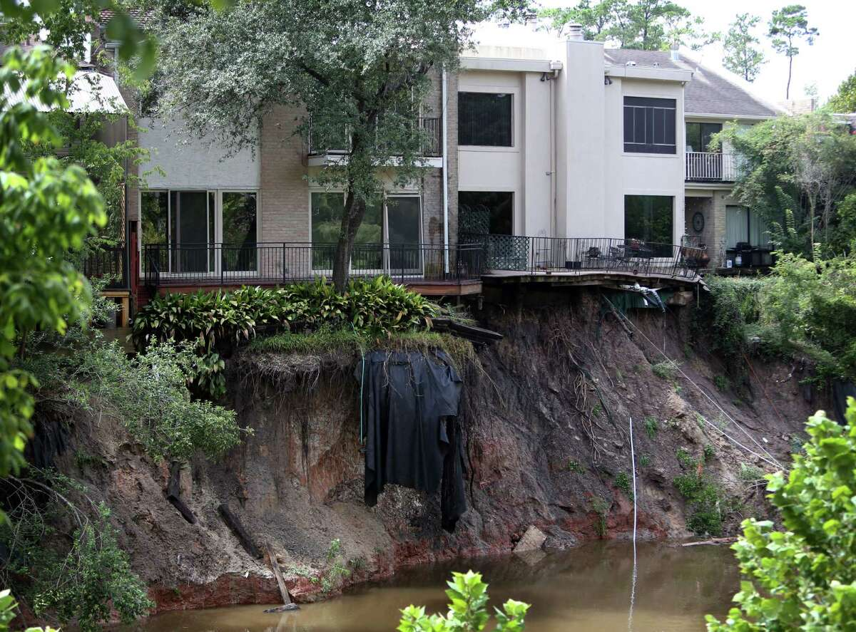 A water hose dangles from one of the Memorial Woods Town Homes after a part of the property collapses into the Spring Branch Bayou due to heavy rains and erosion on Friday, Sept. 19, 2014, in Houston.