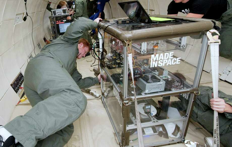 Michael Snyder and Aaron Kemmer monitor the performance of 3-D printer extruders during a microgravity portion of flight aboard a modified Boeing 727. Photo: Uncredited, HONS / Made In Space