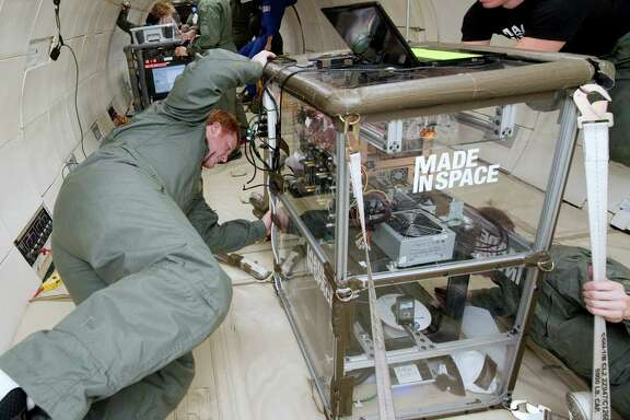 Michael Snyder and Aaron Kemmer monitor the performance of 3-D printer extruders during a microgravity portion of flight aboard a modified Boeing 727.