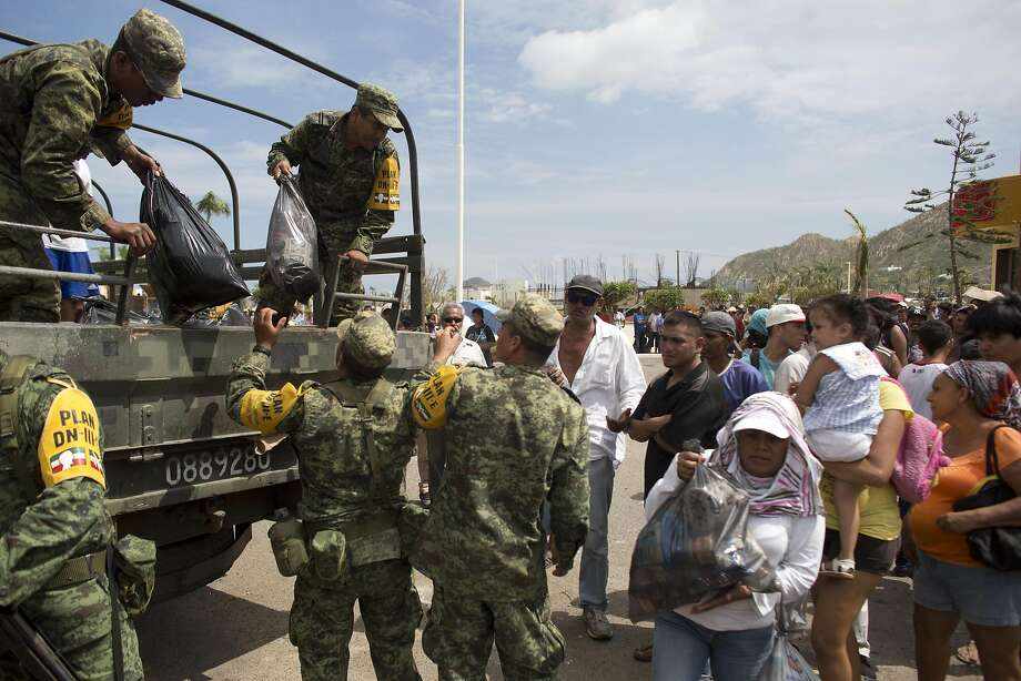 Soldiers distribute food and water to people outside the local Red Cross in the city of Cabo San Lucas, Mexico, Friday, Sept. 19, 2014. Most commerce in the city has halted after power and other utilities were knocked off by hurricane Odile. (AP Photo/Dario Lopez-Mills) Photo: Dario Lopez-Mills, Associated Press